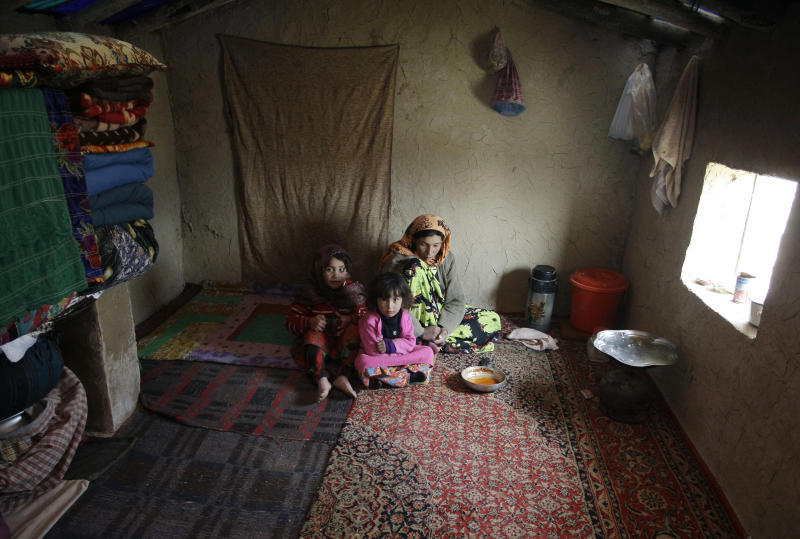 An Afghan internally displaced family sits inside a makeshift house at a refugee camp on the outskirts of Kabul, Afghanistan, Wednesday, Dec. 12, 2012.  More than 2 million Afghans are at risk from cold, disease and malnutrition this winter as an international appeal for funds to help one of the world's poorest countries has fallen drastically short of its goal, the United Nations and several humanitarian agencies warned on Wednesday. (AP Photo/Musadeq Sadeq)