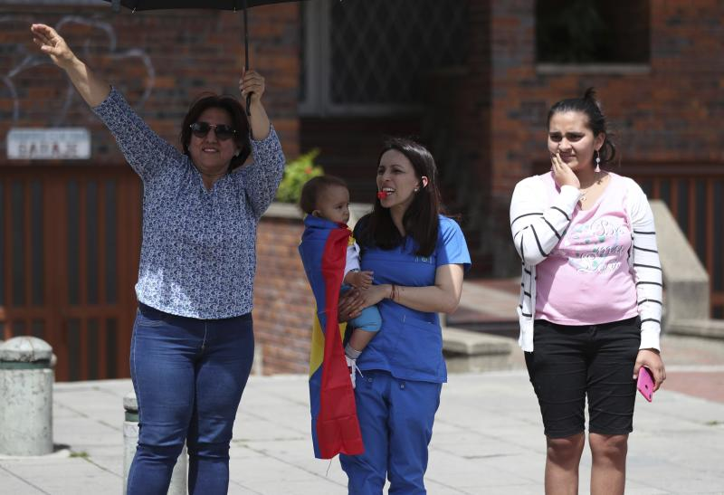Three women show their support for an anti-government march in Bogota, Colombia, Wednesday, Dec. 4, 2019. Colombia's recent wave of demonstrations began with a massive strike on Nov. 21 that drew an estimated 250,000 people to the streets. Protests have continued in the days since but at a much smaller scale. (AP Photo/Fernando Vergara)