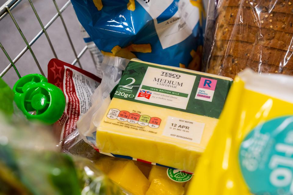 Tesco cheese in a shopping basket with a label showing packaging has been made from recycled plastic