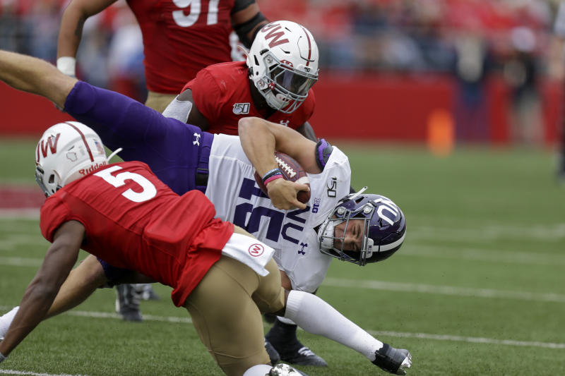 Wisconsin cornerback Rachad Wildgoose (5) and Chris Orr (54) tackle Northwestern quarterback Hunter Johnson (15) during the first half of an NCAA college football game Saturday, Sept. 28, 2019, in Madison, Wis. (AP Photo/Andy Manis)