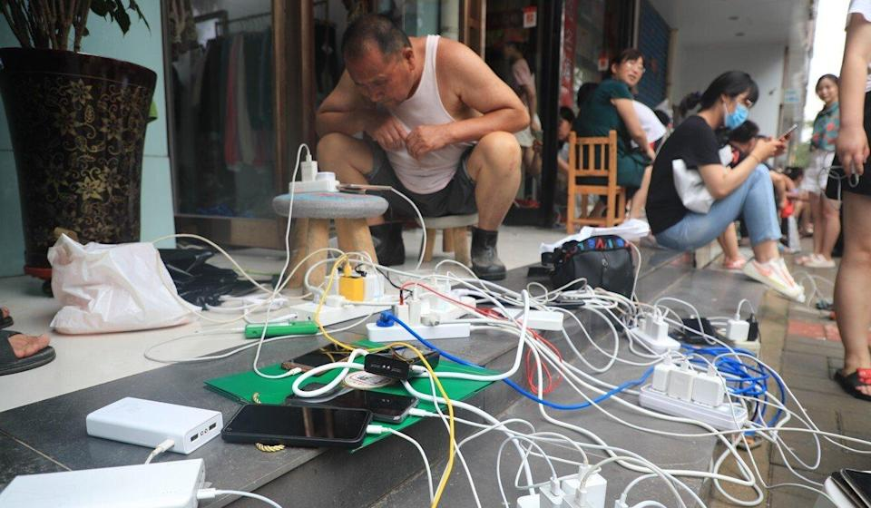 People charge mobile phones outside a shop in Zhengzhou that had electricity. Photo: Getty Images