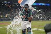 Seattle Mariners catcher Cal Raleigh has water and ice dumped onto him by teammate Tom Murphy as Raleigh takes part in an interview after the Mariners defeated the Oakland Athletics 4-3 in a baseball game Friday, July 23, 2021, in Seattle. (AP Photo/Ted S. Warren)