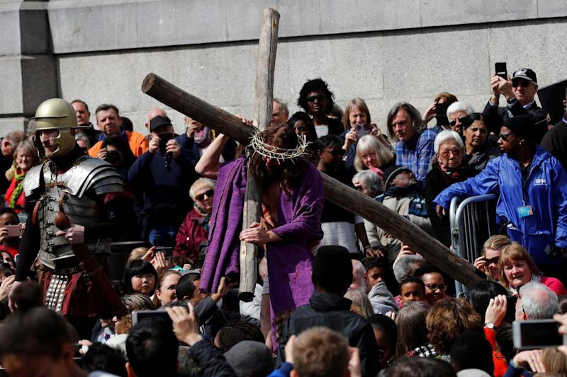 Jesus carries his cross through the crowd while wearing the crown of thorns (Reuters)