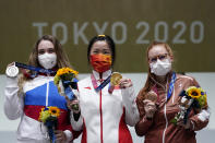 Silver medalist Anastasiia Galashina, left, of the Russian Olympic Committee, gold medalist Yang Qian, of China, center, and bronze medalist Nina Christen, of Switzerland stand after the women's 10-meter air rifle at the Asaka Shooting Range in the 2020 Summer Olympics, Saturday, July 24, 2021, in Tokyo, Japan.(AP Photo/Alex Brandon)