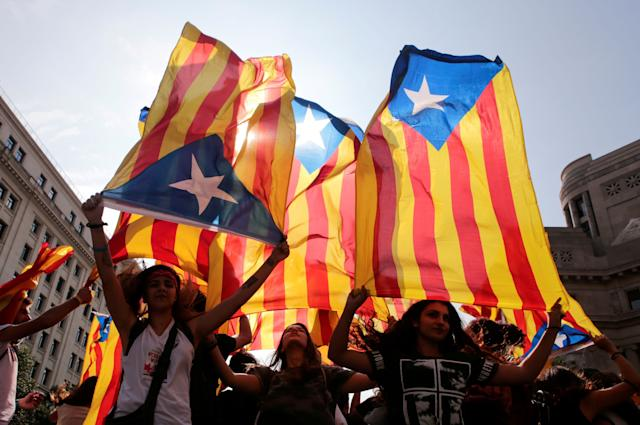 People hold on to Catalan separatist flags on top of an air vent during a demonstration two days after the banned independence referendum in Barcelona, Spain, October 3.