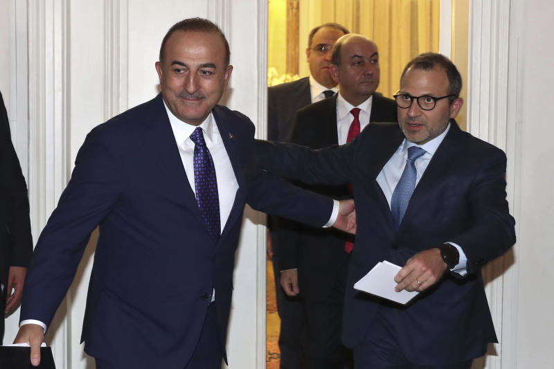 Lebanese Foreign Minister Gibran Bassil, right, with his Turkish counterpart Mevlut Cavusoglu, ahead of a joint press conference, at the Lebanese foreign ministry, in Beirut, Lebanon, Friday, Aug. 23, 2019. (AP Photo/Bilal Hussein)