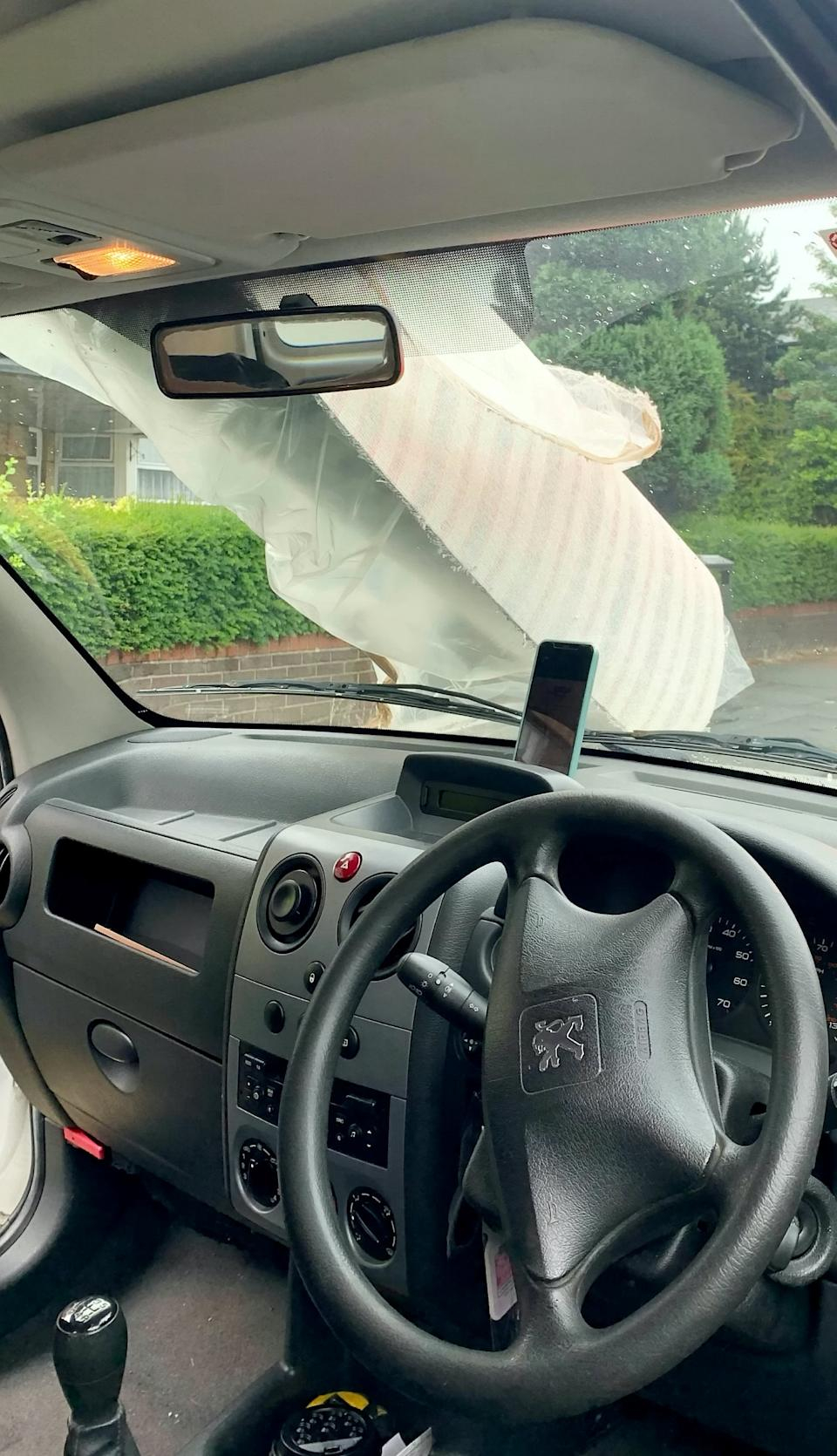A driver was stopped on the M56 with an entire carpet slung over the top of his van obscuring his view.  See SWNS story SWLEcarpet.  July 5, 2021.  Not only had an entire carpet been slung across the length of his van and over the windscreen, it was being driven on the motorway in the pouring rain, said police.
