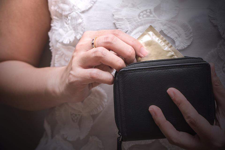 Woman taking a condom out of her wallet