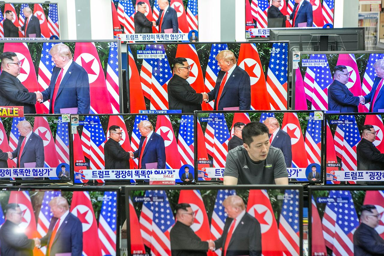 <p>Television screens in a Seoul electronics store display a news broadcast of President Trump and North Korean leader Kim Jong Un shaking hands following a document-signing event in Singapore on Tuesday. (Photo: Jean Chung/Bloomberg via Getty Images) </p>