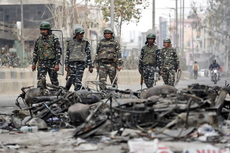 Security forces patrol past charred vehicles in a riot affected area following clashes between people demonstrating for and against a new citizenship law in New Delhi