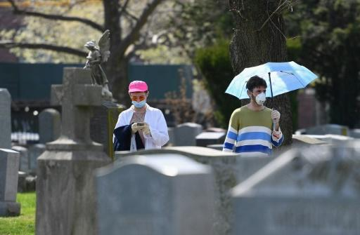 People wearing face masks walk through a cemetery in Brooklyn