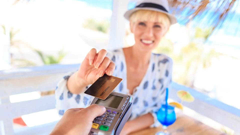 Young woman having fun on beach, using credit card for contactless payment.