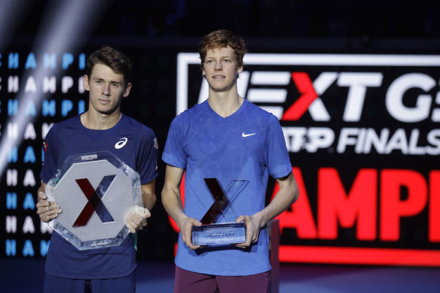 Jannik Sinner, of Italy, right, holds the trophy after beating Australia's Alex De Minaur, left, to win the ATP Next Gen tennis tournament final match, in Milan, Italy, Saturday, Nov. 9, 2019. (AP Photo/Luca Bruno)