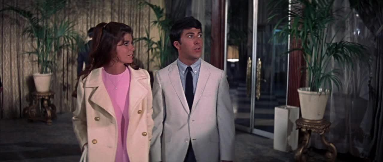 <p>Elaine Robinson (Katharine Ross) dresses like the polar opposite of her mother, her look is always about looking young a fresh. Her look is all about luxurious Americana. The Berkeley students cream colored coat with a pink dress looks like it is straight out of an Ralph Lauren advert. No hints of her mother's fondness for animal print or black are going to be seen here!<br /></p><p>[Photo: Screengrab]<br /></p><p><br /></p>