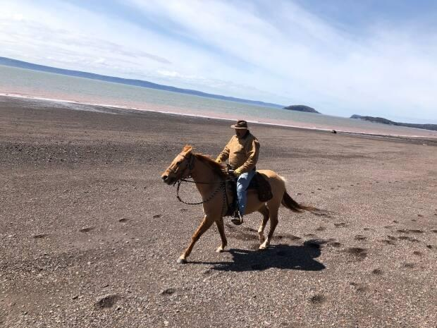 Bill Gilbert rides Sonny along a beach at the Bay of Fundy.