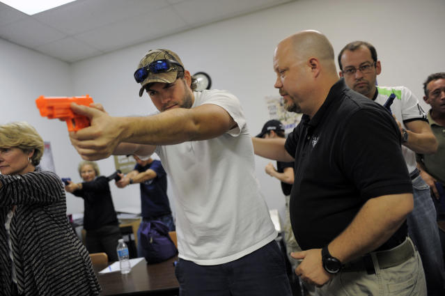 Firearms instructor Mike Magowan (R) works with student Josh Meadows during a concealed weapons permit class at Take Aim Gun Range in Sarasota, Florida December 15, 2012. The number of active concealed weapons licenses in Florida, already home to more owners of such registered weapons than any other U.S. state, is expected to reach the 1 million mark next week, a state official said on Wednesday. REUTERS/Brian Blanco (UNITED STATES - Tags: POLITICS SOCIETY)