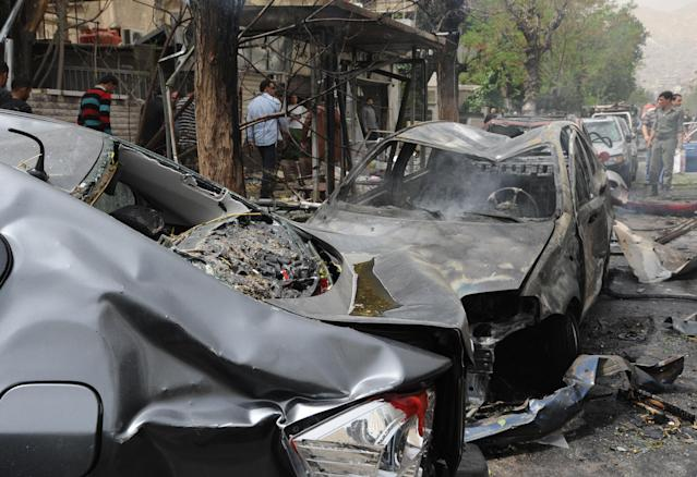 This photo released by the Syrian official news agency SANA, shows Syrians inspecting a damaged car at the scene of a car bomb attack near the Sabaa Bahrat Square, one of the capital's biggest roundabouts, in Damascus, Syria, Monday, April. 8, 2013. A car bomb rocked a busy residential and commercial district in central Damascus, killing at least a dozen people with tens more injured and causing heavy material damage, a Syrian government official said. (AP Photo/SANA)