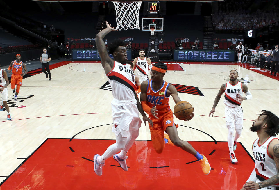 Oklahoma City Thunder guard Shai Gilgeous-Alexander, right, passes the ball around Portland Trail Blazers forward Nassir Little during the first half of an NBA basketball game in Portland, Ore., Monday, Jan. 25, 2021. (AP Photo/Craig Mitchelldyer)