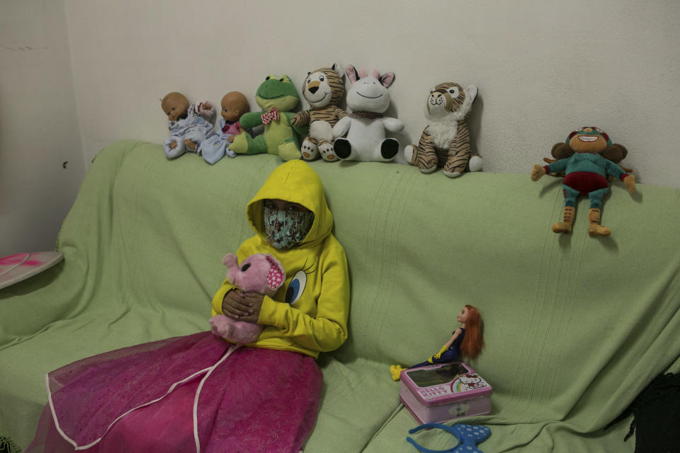 A 10-year-old victim of sexual abuse, who keeps her face covered to hide her identity, poses for a portrait with her stuffed animals inside the Mexican Human Rights Commission (CNDH) headquarters where she has been living with her grandmother, mother, cousin, and two brothers after women's rights activists occupied the building and turned it into a refuge for victims of gender violence almost three months ago in Mexico City, Tuesday, Nov. 17, 2020. The 10-year-old suffered sexual abuse at age 7, which her mother reported to authorities, but it's the more recent abuse of her 11-year-old cousin that led them to leave home and take refuge here. (AP Photo/Ginnette Riquelme)