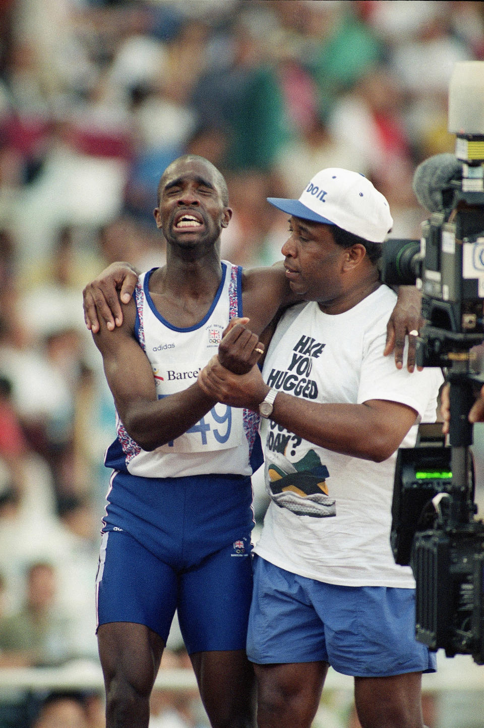 FILE - In this Monday, Aug. 3, 1992, file photo, Britain's Derek Redmond grimaces as he is helped from the track by his father, Jim Redmond, after an injury during the semifinals of the Men's 400-meter race at the Summer Olympics Games in Barcelona (AP Photo/Denis Paquin, File)