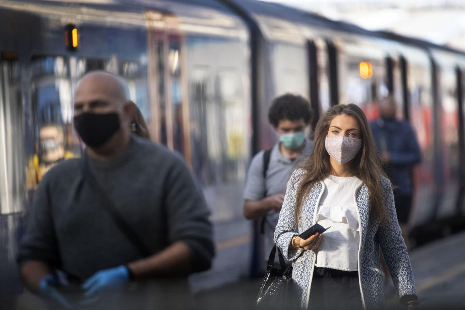 Passengers wearing face masks at Waterloo station as face coverings become mandatory to wear on public transport in the country, with the easing of further lockdown restrictions introduced to combat the spread of coronavirus, in London, Monday June 15, 2020. (Victoria Jones/PA via AP)