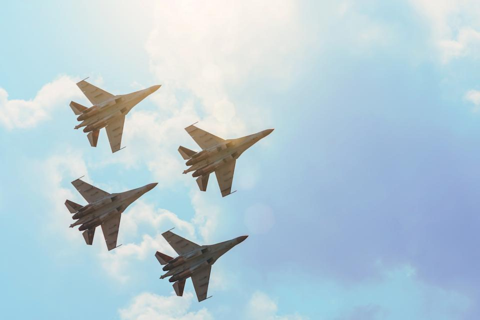 Group of four aircraft fighter jet airplane sun glow toned gradient clouds sky