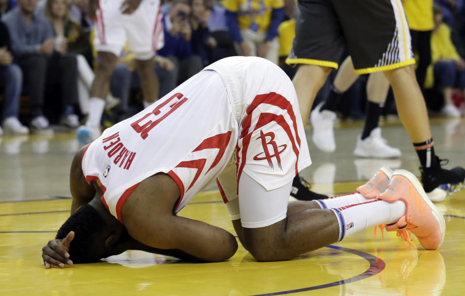 Houston Rockets' James Harden kneels on the court with an apparent injury during the first half of Game 2 of the team's second-round NBA basketball playoff series against the Golden State Warriors in Oakland, Calif., Tuesday, April 30, 2019. (AP Photo/Jeff Chiu)