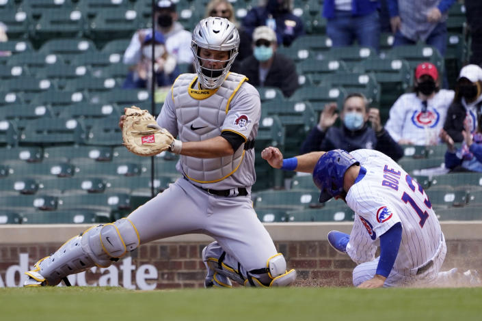 Chicago Cubs' David Bote (13) scores past Pittsburgh Pirates catcher Jacob Stallings, on a single by Joc Pederson, during the second inning of a baseball game Friday, May 7, 2021, in Chicago. (AP Photo/Charles Rex Arbogast)