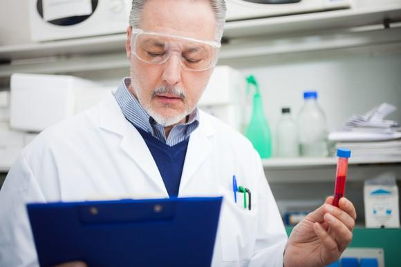 A biotech lab researcher reading a clipboard with a vial of blood in his left hand.
