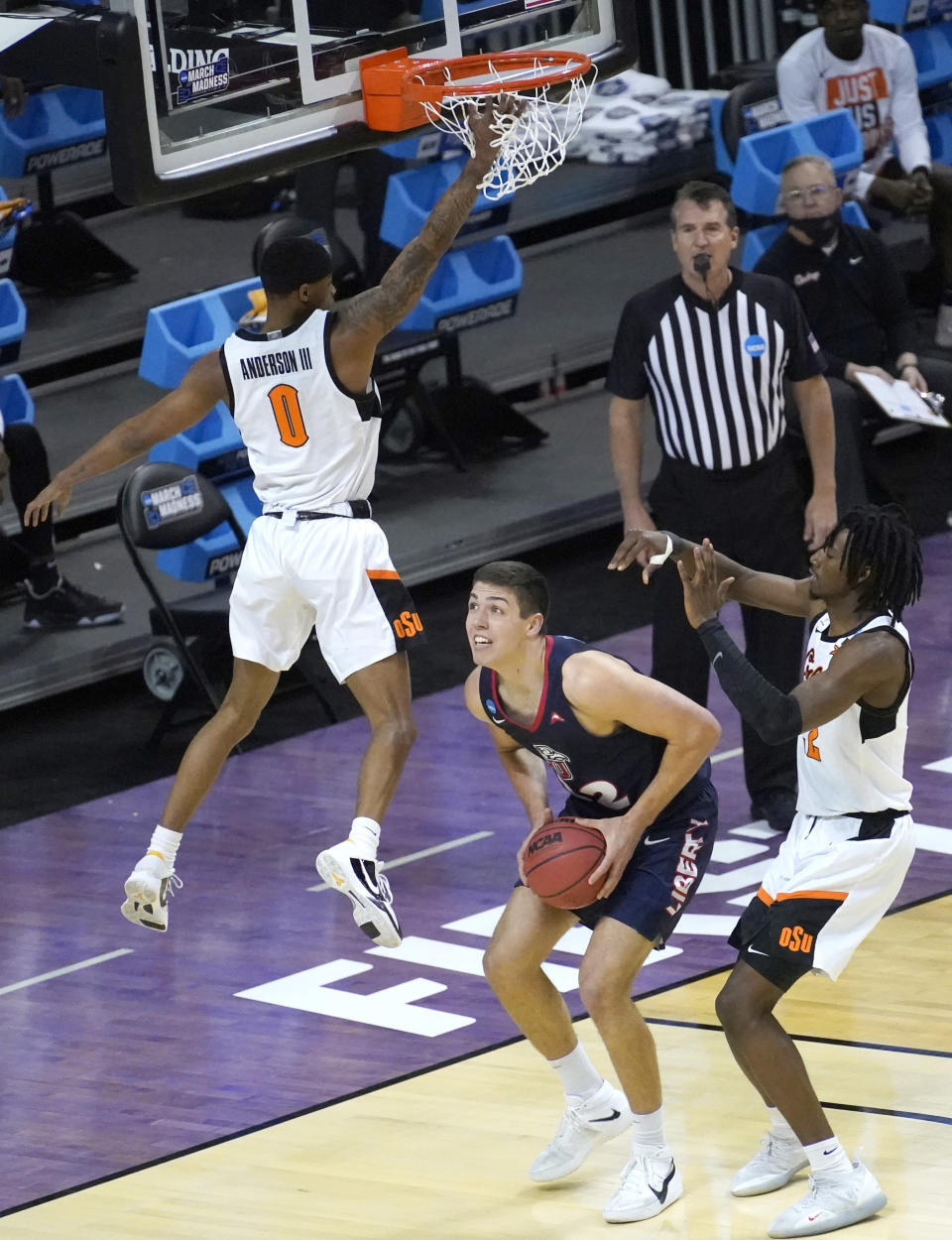 Liberty's Blake Preston, center, pump fakes Oklahoma State guard Avery Anderson III in to the air as Kalib Boone also defends during the first half of a first round NCAA college basketball game Friday, March 19, 2021, at the Indiana Farmers Coliseum in Indianapolis.(AP Photo/Charles Rex Arbogast)