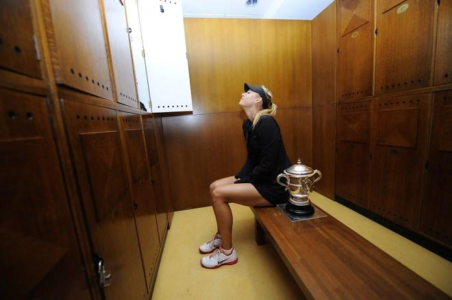 TOPSHOTS Russia's Maria Sharapova poses with her trophy in the clockrooms after winning against Italy's Sara Errani the Women's Singles final tennis match of the French Open tennis tournament at the Roland Garros stadium, on June 9, 2012 in Paris.   AFP PHOTO / POOL SINDY THOMASSINDY THOMAS/AFP/GettyImages