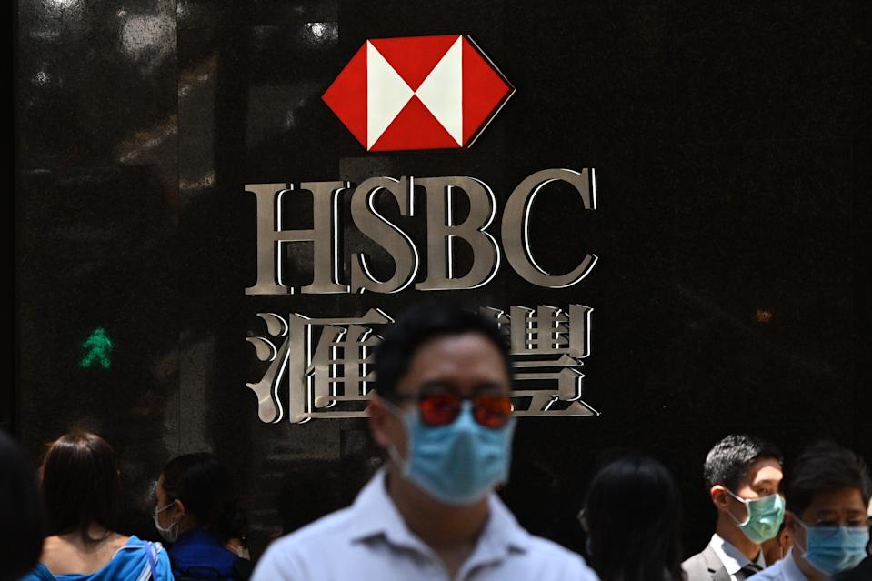 Pedestrians wear face masks as they walk past HSBC signage outside a branch of the bank in Hong Kong on April 28, 2020. - HSBC on April 28 said first quarter pre-tax profits almost halved as the banking giant was battered by the global coronavirus pandemic while it embarked on a major restructuring. (Photo by Anthony WALLACE / AFP) (Photo by ANTHONY WALLACE/AFP via Getty Images)