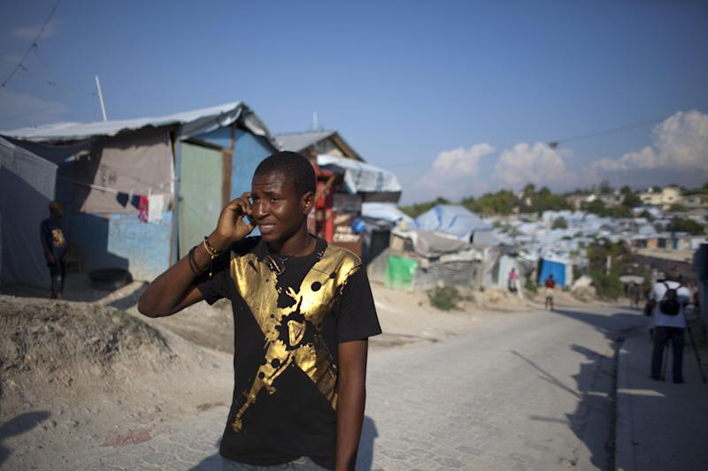 In this April 24, 2013 photo, Darlin Lexima speaks on the phone as he walks through Camp Acra in Port-au-Prince, Haiti. Lexima, 21, who lives in the camp for people displaced by the 2010 earthquake, was arrested by police early April 15 when he was walking home from a disco club as police were responding to residents protesting an earlier raid by an unidentified band of motorcyclist who set fire to their homes. In the few weeks since the mid-April confrontation, it has become an instant symbol for what many say is the growing use of threats and sometimes outright violence to clear out sprawling displaced person camps, where some 320,000 people still live. (AP Photo/Dieu Nalio Chery)