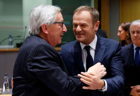 EU Commission President Juncker greets EU Council President Tusk during the Tripartite Social Summit in Brussels
