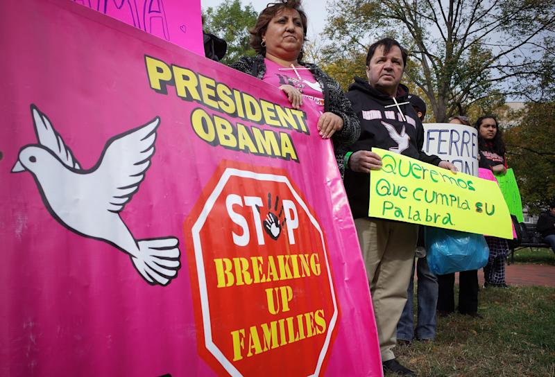 Immigration activists hold a banner and placards during a rally calling for immigration reform at Lafayette Square in Washington, DC on November 3, 2014 (AFP Photo/Mandel Ngan)