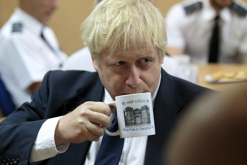 Britain's Prime Minister Boris Johnson takes a drink from a prison mug as he talks with prison staff during a visit to HM Prison Leeds, in Leeds, Britain August 13, 2019. Jon Super/Pool via REUTERS