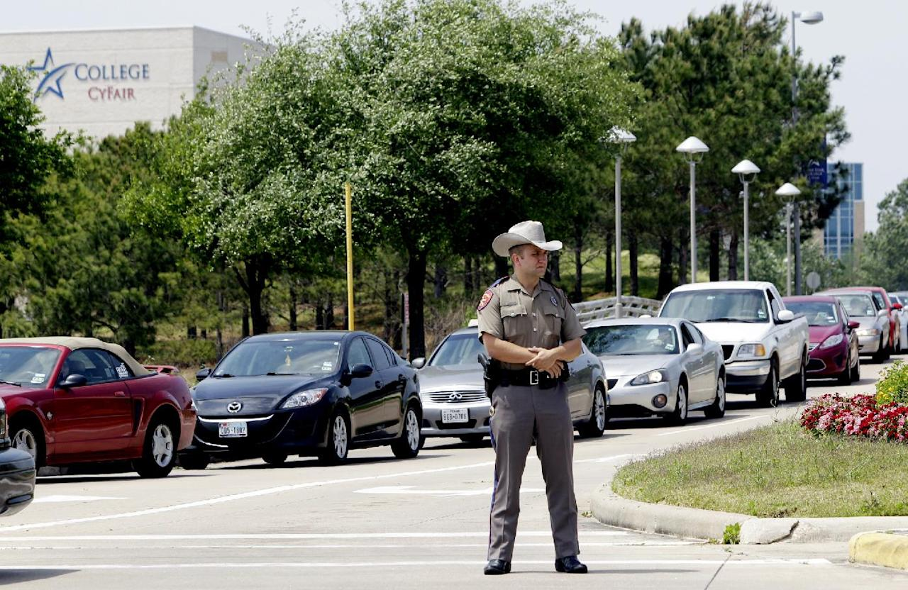 A Texas State Trooper stands at an entrance as vehicles leave from the Cy-Fair campus of Lone Star Community College in Cypress, Texas on Tuesday, April 9, 2013. More than a dozen people were wounded when a suspect went building-to-building in an apparent stabbing attack at the college campus authorities said. The attack on the Lone Star Community College System's campus in Cypress sent at least 12 people to area hospitals, including four people taken by helicopter, according to Cy-Fair Volunteer Fire Department spokesman Robert Rasa. (AP Photo/Houston Chronicle, Melissa Phillip) MANDATORY CREDIT