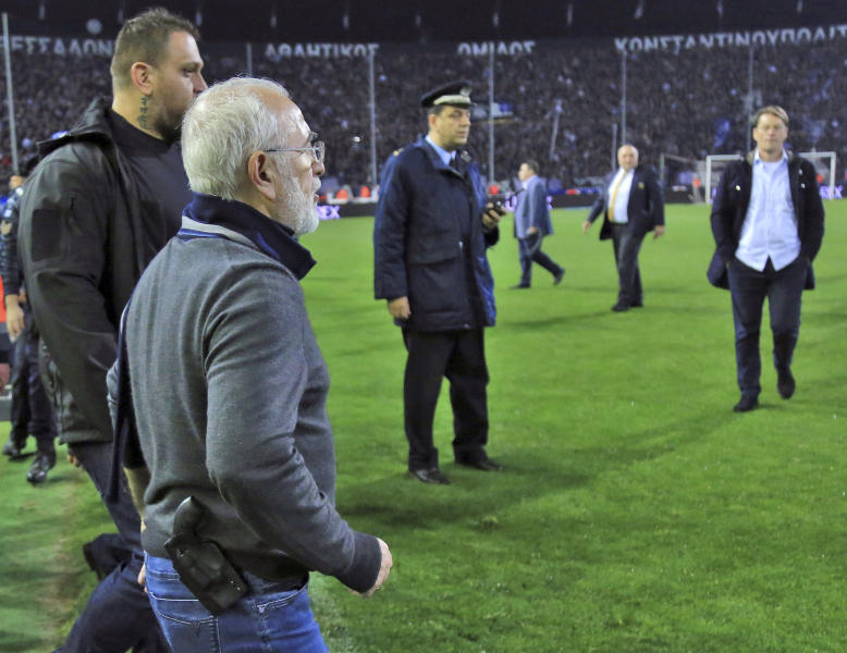 PAOK owner, businessman Ivan Savvidis invades into the pitch during the Greek League soccer match between PAOK and AEK Athens in the northern Greek city of Thessaloniki, Sunday, March 11, 2018. Savvidis invaded the pitch twice. The second time, without the overcoat he was wearing before, a pistol was clearly visible in its holder. AEK officials claim Savvidis threatened the referee during his first foray into the pitch, before being pulled away by his retinue. (InTime Sports via AP)