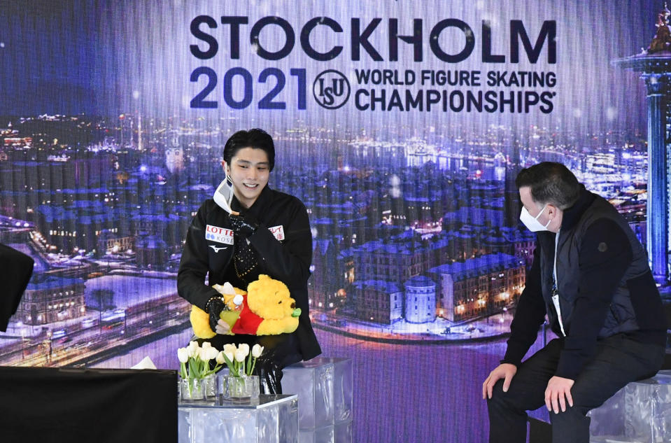 Yuzuru Hanyu of Japan sits with his coach after this performance at the Men Short Program at the Figure Skating World Championships in Stockholm, Sweden, Thursday, March 25, 2021. (AP Photo/Martin Meissner)