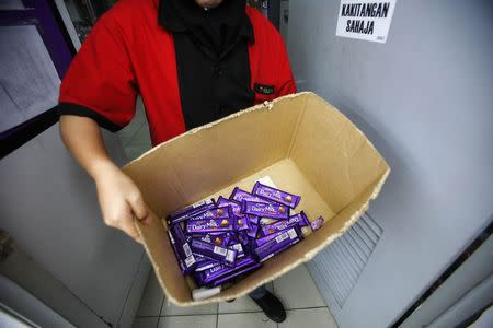 An employee shows a box containing Cadbury Dairy Milk Hazelnut and Cadbury Dairy Milk Roast Almond, to be return tomorrow in a shop in Shah Alam