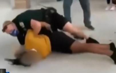 Screen grab from social media video shows school resource officer in Liberty High School in Kissimmee, Florida beginning to handcuff female student he'd slammed to the ground in a hallway. / Credit: WKMG-TV