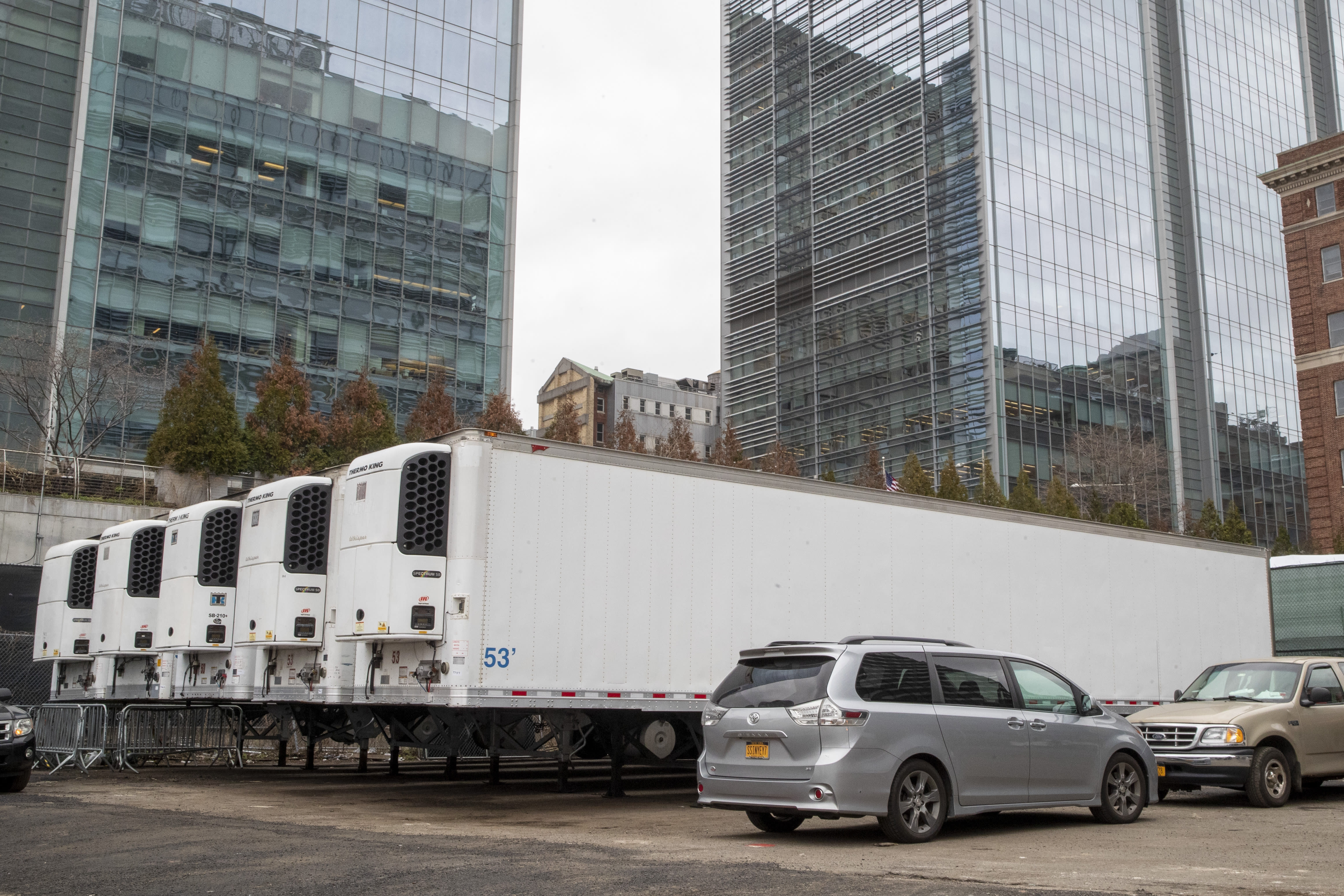 Refrigerated trailers are seen parked at the site of a makeshift morgue being built in New York, Wednesday, March 25, 2020. New York officials are keeping a close eye on already-stressed hospitals as the number of cases is projected to rise for perhaps three more weeks. The new coronavirus causes mild or moderate symptoms for most people, but for some, especially older adults and people with existing health problems, it can cause more severe illness or death. (AP Photo/Mary Altaffer)