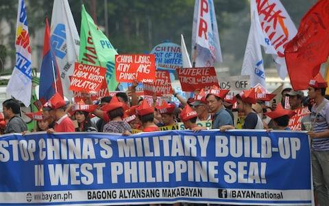 Activists carry placards during a protest in front of the Chinese consulate in Manila on February 10, 2018, against Beijing's claims in the South China Sea  - Credit: AFP