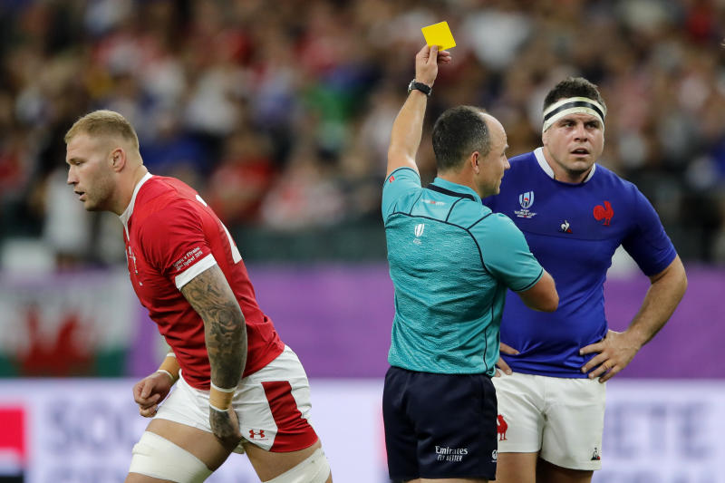 Referee Jaco Peyper gives a yellow card to Wales' Ross Moriarty, left, during the Rugby World Cup quarterfinal match at Oita Stadium in Oita, Japan, Sunday, Oct. 20, 2019. (AP Photo/Christophe Ena)