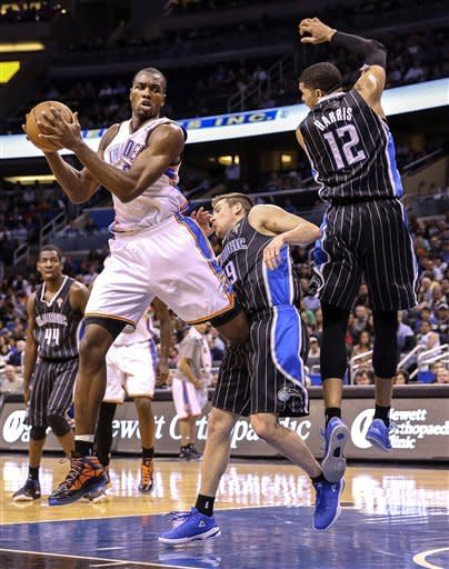 Oklahoma City Thunder's Serge Ibaka, fron left, grabs an offensive rebound against Orlando Magic's Tobias Harris (12) and Beno Udrih during the second half of an NBA basketball game on Friday, March 22, 2013, in Orlando, Fla. The Thunder won 97-89. (AP Photo/Willie J. Allen Jr.)