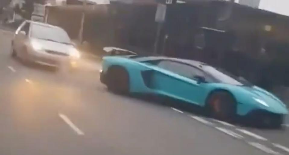 A shot of a aqua Lamborghini shortly before it is rear-ended by a silver Ford Fiesta
