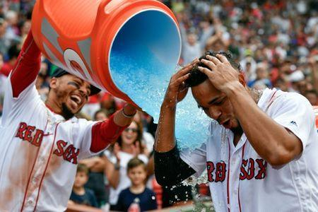 Jul 14, 2018; Boston, MA, USA; Boston Red Sox right fielder Mookie Betts (50) pours gatorade on to shortstop Xander Bogaerts (2) after scoring a walk off grand slam against the Toronto Blue Jays during the tenth inning at Fenway Park. Mandatory Credit: Brian Fluharty-USA TODAY Sports