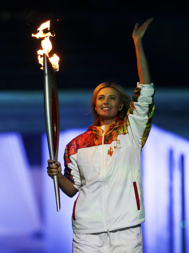 Russian tennis player Maria Sharapova carries the Olympic torch during the opening ceremony of the 2014 Winter Olympics in Sochi, Russia, Friday, Feb. 7, 2014. (AP Photo/Mark Humphrey)