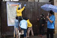 BMC officials hang a notice on the main door of the residence of Bollywood star Amitabh Bachchan as he tested positive for COVID-19 in Mumbai on July 12, 2020. - Bollywood megastar Amitabh Bachchan, 77, tested positive for COVID-19 on July 11 and was admitted to hospital in Mumbai, with his actor son Abhishek -- who also announced he had the virus -- saying both cases were mild. (Photo by Sujit Jaiswal / AFP)
