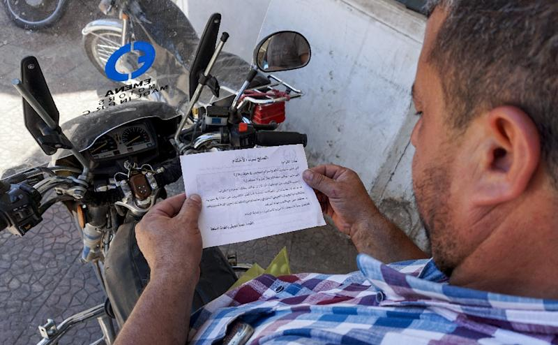 Government helicopters have dropped leaflets over towns in Idlib's eastern countryside urging people to surrender (AFP Photo/OMAR HAJ KADOUR)